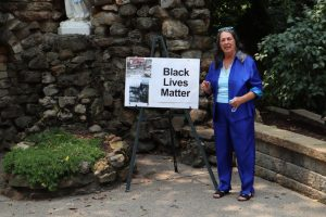 Woman standing with Black Lives Matter sign on easel.